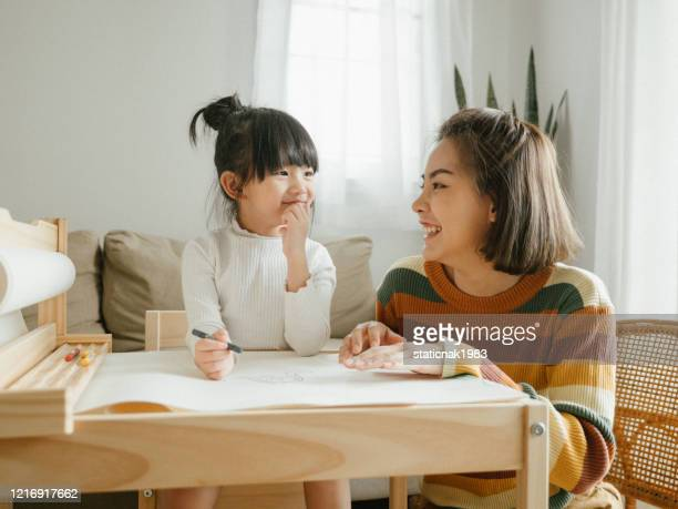 happy asian boy painting with crayon with his mother in living room at home. - family with one child stock pictures, royalty-free photos & images
