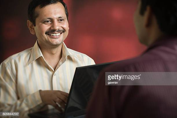 Happy Asian business man with laptop talking to his client.