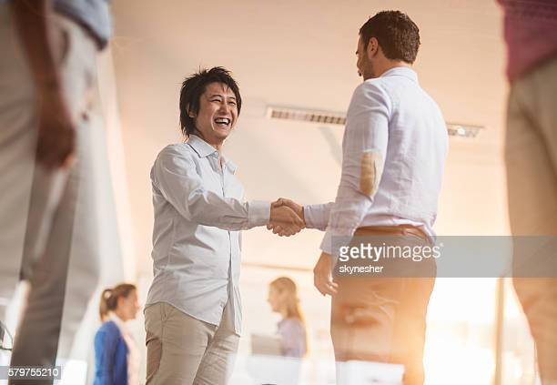 Happy Asian businessman shaking hands with his coworker.