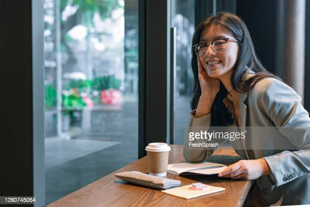 happy asian businesswoman writing a weekly plan in her agenda before going to the office - monday stock pictures, royalty-free photos & images
