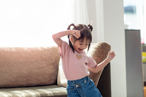 Happy Asian child having fun and dancing in a room 1155438455