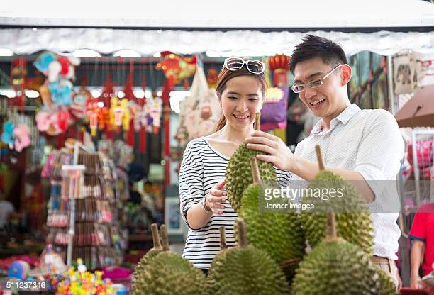 Happy Asian couple buying a Durian fruit.