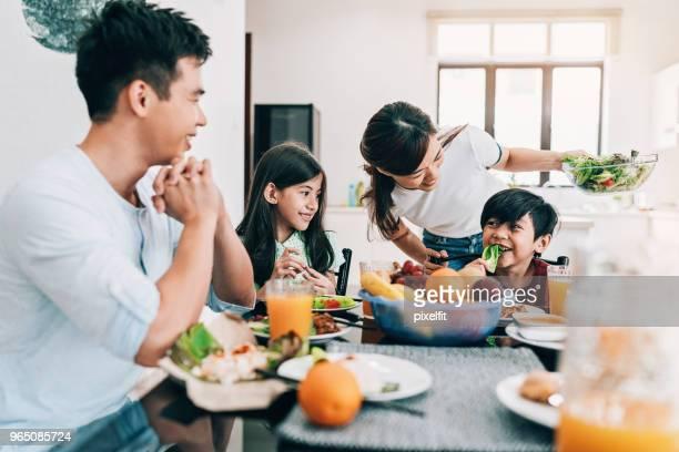 テーブルでアジア民族の幸せ家族 - 食卓 ストックフォトと画像
