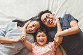Happy Asian family laying on bed in bedroom with happy and smile, top view