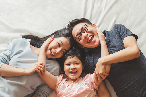 Happy Asian family laying on bed in bedroom with happy and smile, top view 1142407009