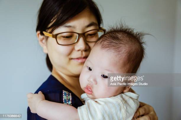 happy asian family, mother holding baby in her arms. - japanese breastfeeding stock pictures, royalty-free photos & images