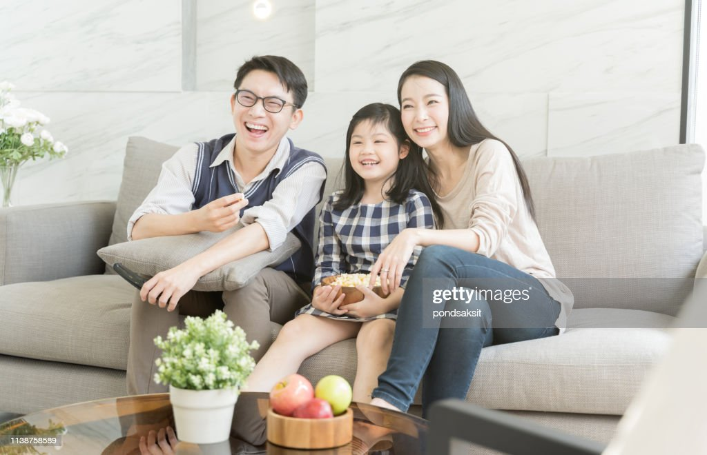 happy asian family watching tv together on sofa in living room. family and home concept. : Stock Photo