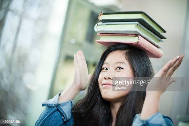 Glücklich asiatische Mädchen-student balancing Stapel von Büchern über Kopf.