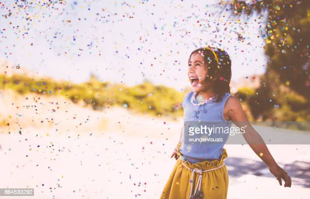 Happy Asian girl throwing confetti in the air and laughing