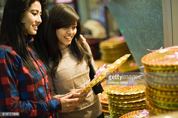Happy Asian girls buying gifts in a shop before festival.