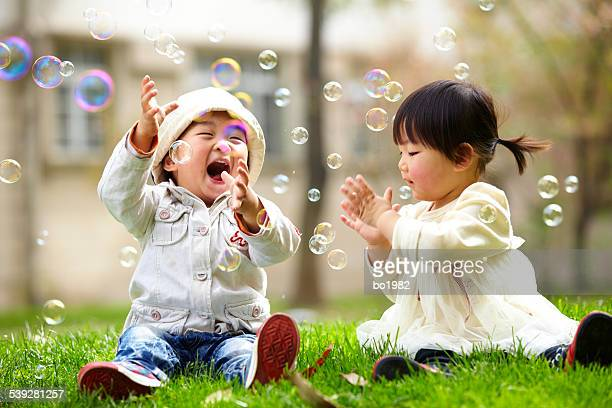 happy asian kids playing bubble together