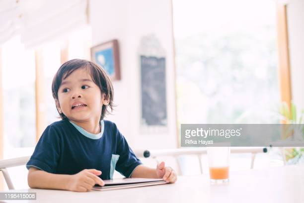 happy asian little boy reading book - rifka hayati stock pictures, royalty-free photos & images