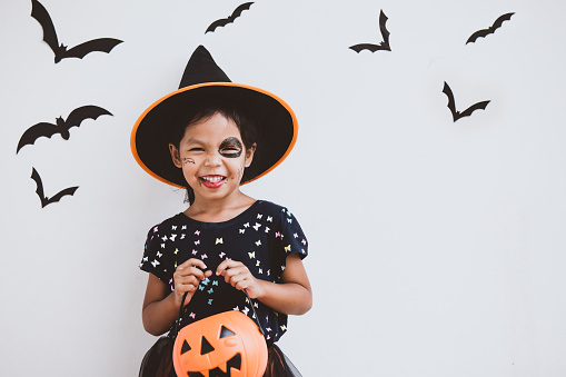 Happy asian little child girl in costumes and makeup having fun on Halloween celebration 1027435208