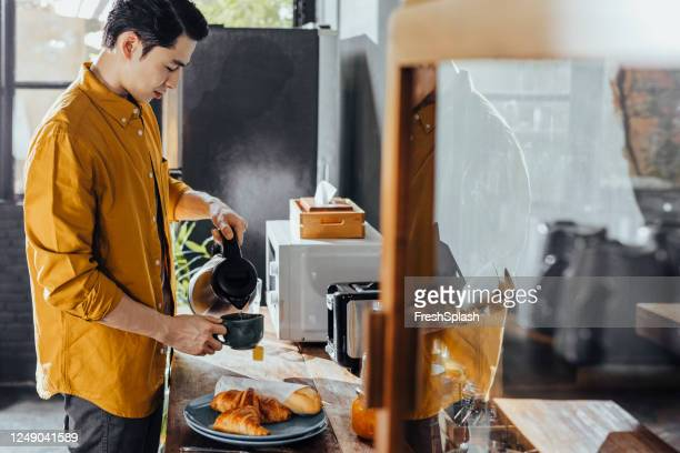 happy asian man in a yellow shirt making tea in the kitchen in the morning - kettle stock pictures, royalty-free photos & images