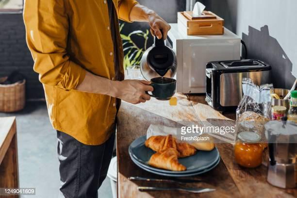 朝の台所でお茶を作る幸せなアジア人 - やかん ストックフォトと画像