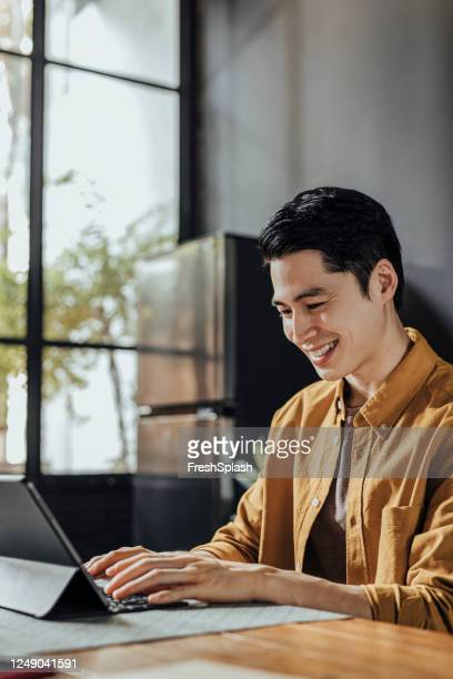 happy asian man working on his digital tablet computer at home - yellow stock pictures, royalty-free photos & images