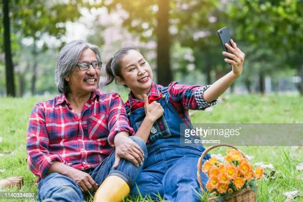 Happy Asian mature couple taking a selfie or video conference with smart phone at park outdoors