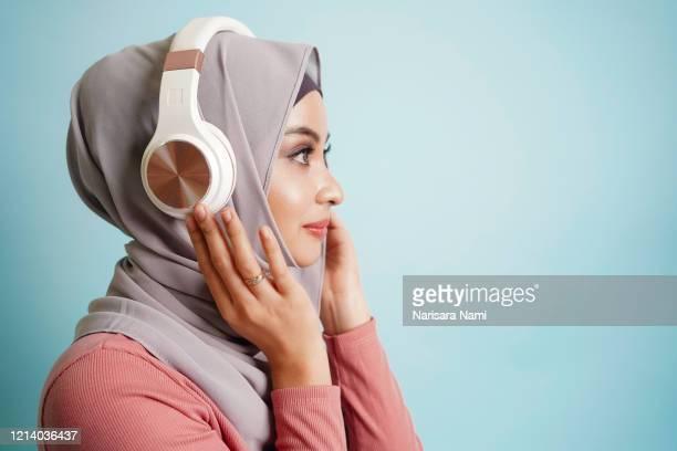 happy asian muslim teenage girl listen the audio music in wireless headphone from mp3 technology. - ブルートゥース ストックフォトと画像