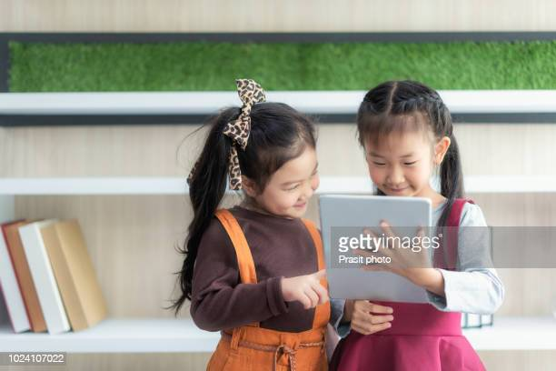 happy asian preschool students at school and playing with pc tablet together in classroom. education and technology concept. - very young thai girls stock photos and pictures