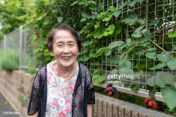 幸せなアジアの先輩女性は、外で笑顔 - 80代 ストックフォトと画像