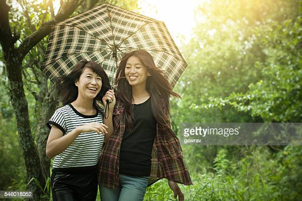 Happy Asian teenage friends walking under umbrella in nature.