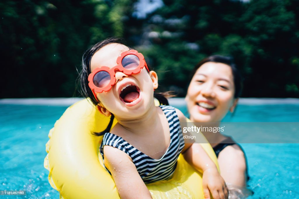 Happy Asian toddler girl with sunglasses smiling joyfully and enjoying family bonding time with mother having fun in the swimming pool in summer : Stock Photo