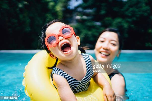 happy asian toddler girl with sunglasses smiling joyfully and enjoying family bonding time with mother having fun in the swimming pool in summer - vacaciones viajes fotografías e imágenes de stock