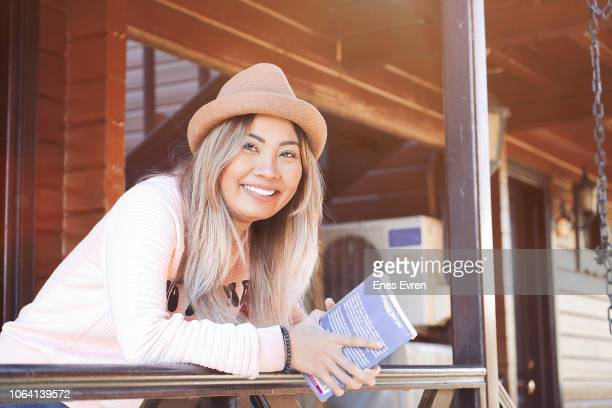 Happy Asian woman in countryside hotel reading a book