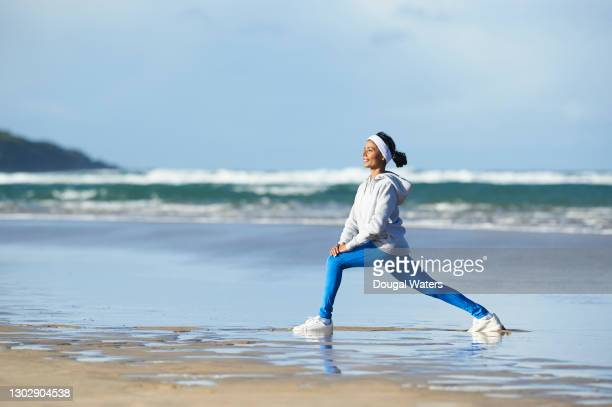 happy asian woman in sportswear stretching legs at beach. - active lifestyle stock pictures, royalty-free photos & images