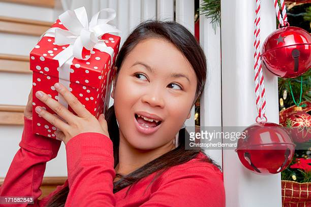 happy asian woman listening to christmas gift - shaking stock pictures, royalty-free photos & images