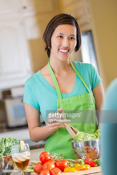 Happy Asian woman preparing salad at home in kitchen