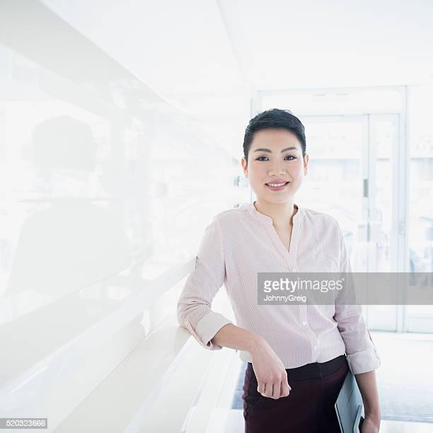 Happy Asian woman smiling in modern office, portrait