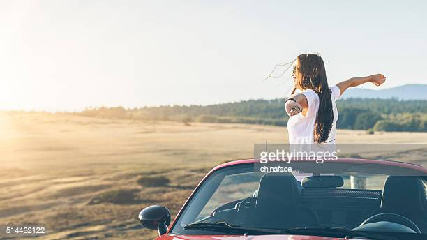 happy asian woman standing in car with arms raised - american woman stock photos and pictures