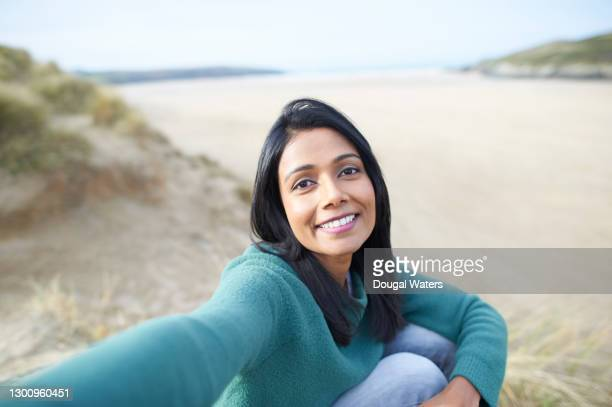 happy asian woman taking selfie at beach. - dougal waters stock pictures, royalty-free photos & images
