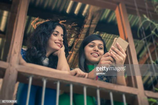 happy asian young women sharing mobile phone together. - salwar kameez stock pictures, royalty-free photos & images
