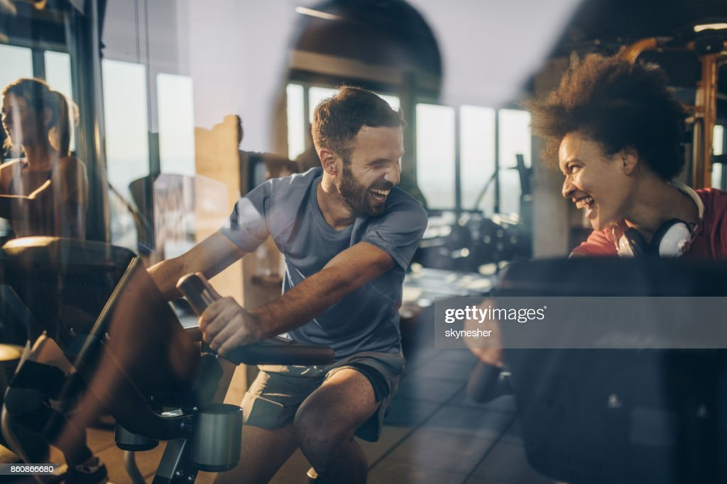 Happy athletes communicating and laughing while exercising in a gym together. : Stock Photo