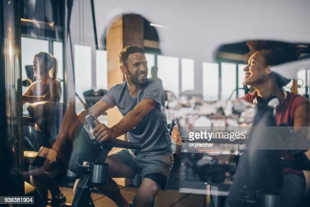 gelukkig atleten communiceren tijdens het sporten in een sportzaal samen. - fitness stockfoto's en -beelden