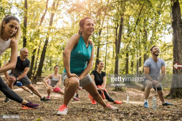 Happy athletes doing stretching exercises while working out in in nature.