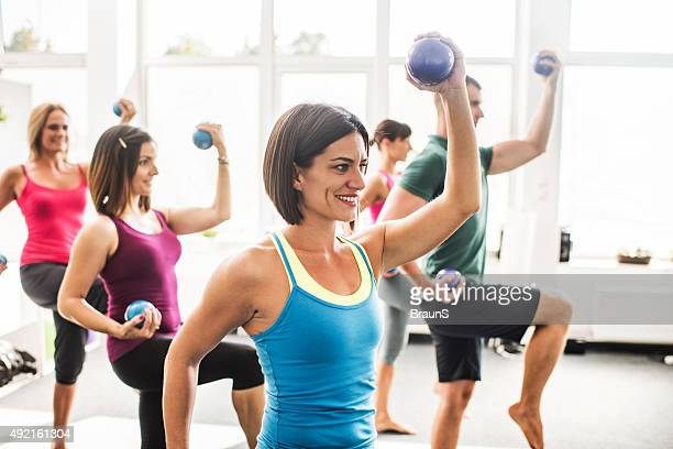 Happy athletes exercising with weight balls on Pilates class.