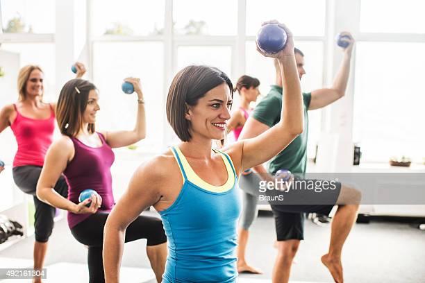 Heureux sportifs de l'exercice avec poids en cours de Pilates.