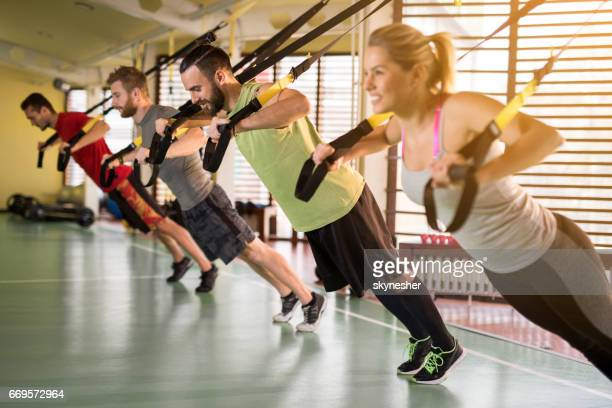 Happy athletes having a suspension training in a health club.