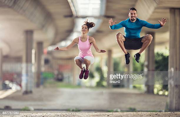 Happy athletes jumping high up on sports training outdoors.