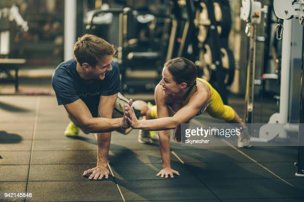 Happy athletic couple cooperating while doing push-ups in a gym.