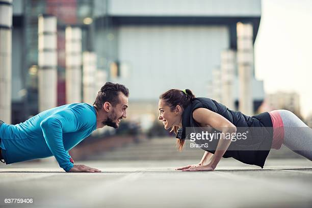 Happy athletic couple doing push-ups together on the street.