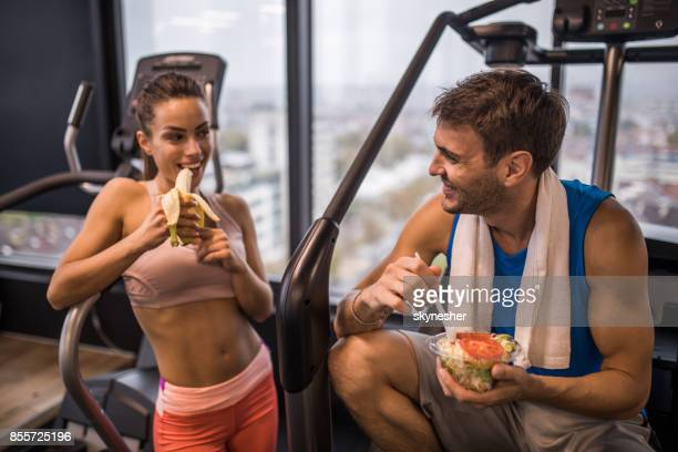 happy athletic couple eating healthy food on a break in a gym. - man eating woman out stock photos and pictures