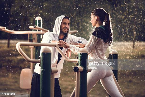 Happy athletic couple flirting at outdoor gym on a rain.