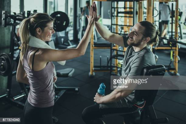 Happy athletic couple giving high-five to each other after sports training.