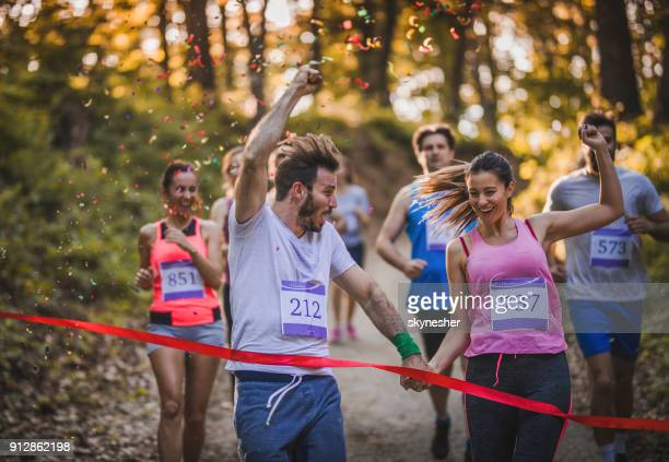 happy athletic couple holding hands while running through finish line together. - finishing line stock pictures, royalty-free photos & images