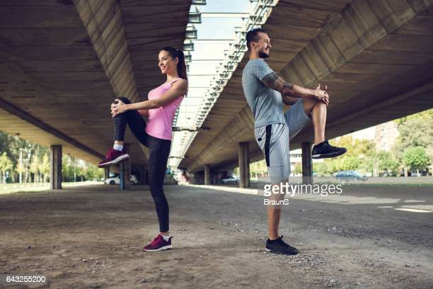 happy athletic couple stretching back to back on the street. - standing on one leg stock pictures, royalty-free photos & images