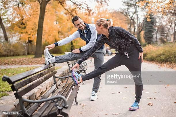 Heureux couple athlétique étirer ses jambes sur un banc.